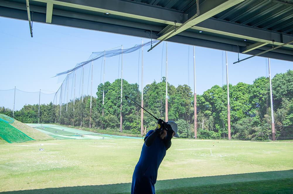 ゴルフの打ちっ放し練習をする女性