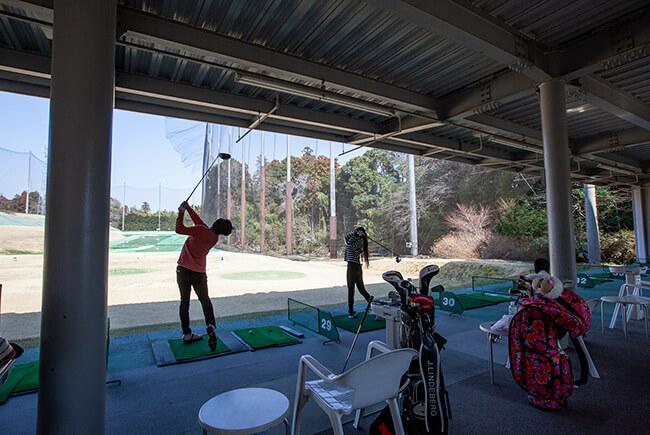 ゴルフの打ちっ放し練習をするカップル