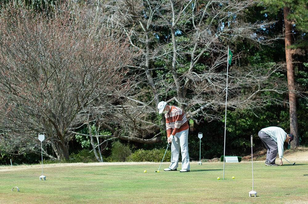 ベントグリーンでゴルフを楽しむ人々